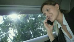 The young beautiful businesswoman communicates by phone sitting in a limousine - stock footage