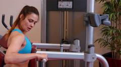 Woman using weights machine in gym Stock Footage