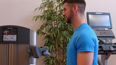 Woman using weights machine in gym with trainer Stock Footage
