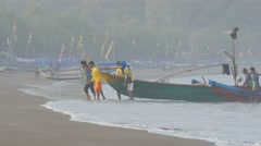 Men carrying fisher boat from sea,Pangandaran,Java,Indonesia Stock Footage