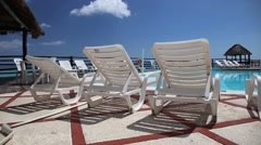 Lounge sunbeds near swimming pool - stock footage