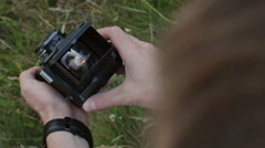 Vintage camera in hands, sunset in viewfinder - stock footage