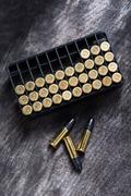 Scattering of small caliber cartridges on a wooden background - stock photo
