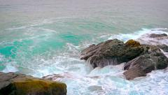 Ocean waves wash over the barnacle encrusted surface of natural boulders Stock Footage