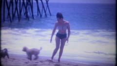 2620 - young woman plays on the beach with dogs - vintage film home movie Stock Footage