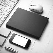 computer and brown notebook with office supplies black and white style - stock photo