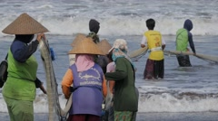 Ladies with conical hat pulling fisher net from sea,Pangandaran,Java,Indonesia Stock Footage