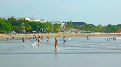Begginers practice on serfing boats in small waves on popular Kuta beach Stock Footage