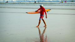Surfer in red dress and halmet get out the sea with yellow surfing board Stock Footage