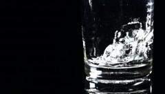 Slow motion shot of water being poured into a glass, swirling and bubbling Stock Footage