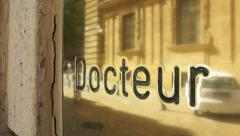 Doctor sign plaque made from gold with reflection of the city and pedestrians Stock Footage
