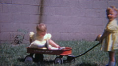 1965: Twin toddler girls dressed identically red wagons outdoors. Stock Footage