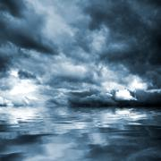 Dark storm clouds before rain above the water level. Stock Photos
