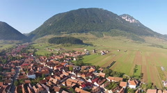 Village at the base of a mountain ridge, aerial view Stock Footage