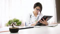 Busy spectacles woman doctor taking notes on clipboard computer, low shot - stock footage