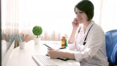 Attractive woman doctor talking on phone in exam room, dolly shot - stock footage