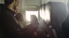 Young family with a child sit inside an airplane and play with a teddy bear Stock Footage