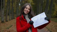 Young beautiful woman showing 25 number on sheet of paper in the autumn park. - stock footage