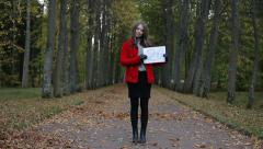 Young beautiful woman showing 20 number on sheet of paper in the autumn park. Stock Footage