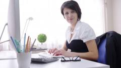 Formal wear businesswoman working, typing and looking at camera, smiling Stock Footage
