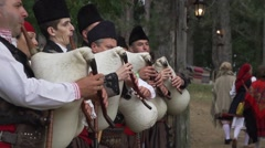 Bulgarian bagpipers in costumes play festival in forest Stock Footage