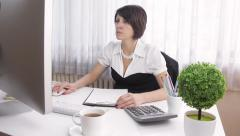 Attractive serious accountant businesswoman working, contemporary office, dolly Stock Footage