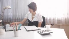 Attractive serious accountant businesswoman working, contemporary office, dolly - stock footage
