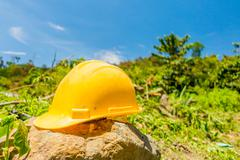Yellow hard hat with a coffee plantation farm in the background - stock photo