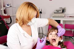 female dentist treats tooth little girl - stock photo