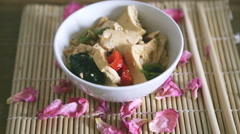 spicy tofu and in a bowl  with chosticks for a solitary meal - stock footage