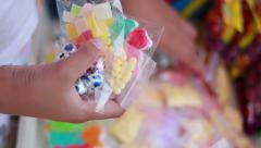 Little girl holds colorful sweet candy in the store Stock Footage
