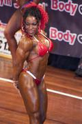 Female bodybuilder in triceps pose and red bikini Stock Photos