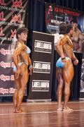 Bodybuilding duo in relaxed side pose on stage Stock Photos