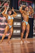 Bodybuilding duo in front double biceps pose on stage Stock Photos