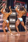 Bodybuilding duo in back double biceps pose on stage Stock Photos
