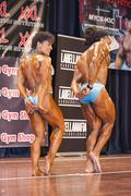 bodybuilding duo in triceps pose on stage - stock photo