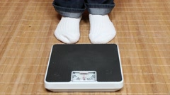 Overweight woman on a bathroom weight. Stock Footage