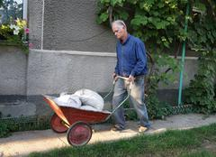 Man with barrow full of cement bags Stock Photos