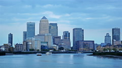 Boats floating on river Thames at sunset, London, Canary Wharf on the background Stock Footage
