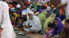 Indian people eating free food at soup kitchen in Golden Temple. Amritsar, India Stock Footage