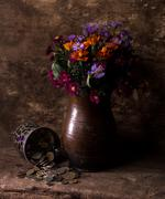 Flowers in vase and pile of old coins - stock photo
