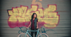 Teen girl standing with her bicycle on a city street Stock Footage