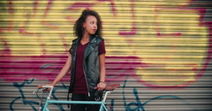 African American teen girl with her bicycle on a sidewalk Stock Footage