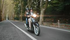 Couple riding their scooter smiles and waves hands Stock Footage