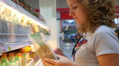 Young Woman at Supermarket Using Smartphone Stock Footage