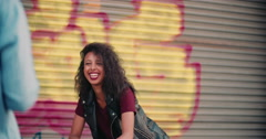 Teenage girl smiling at someone on a city street Stock Footage