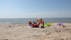 Small boy playing with toys on the beach Stock Footage