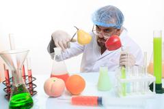 scientist fills chemicals fruit and vegetables - stock photo