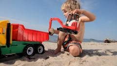 Boy loads sand with the help of excavator in the truck Stock Footage