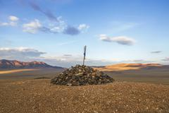 Stock Photo of Pile of stones serving as a reference point on  mountain road